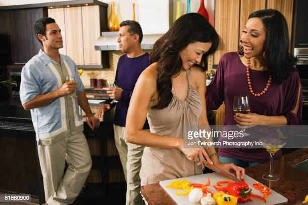 Multi-ethnic friends drinking and preparing food