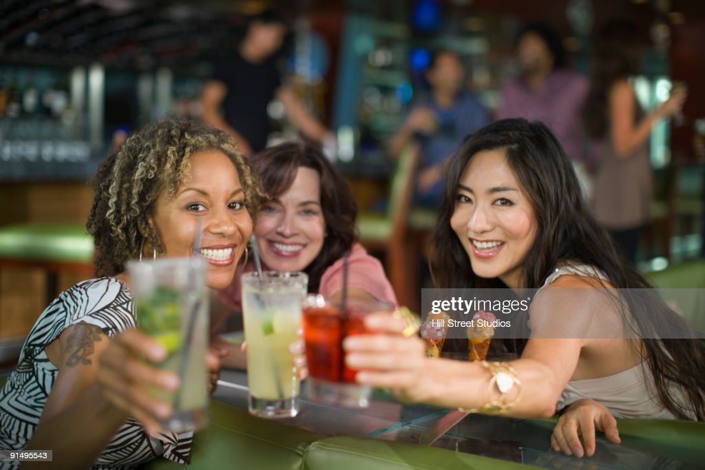 Multi-ethnic friends drinking cocktails in nightclub : Stock Photo