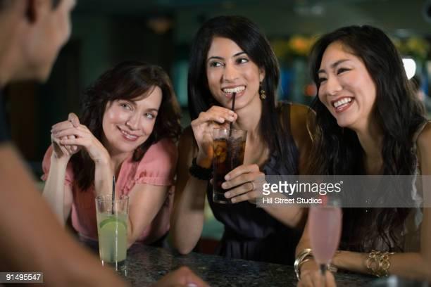 Multi-ethnic friends drinking cocktails in nightclub