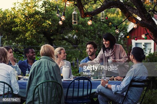 Multi-ethnic friends enjoying dinner party at yard