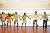 Multi-ethnic friends holding hands at beach resort
