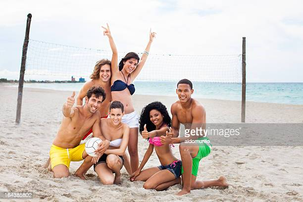 Multi-ethnic friends on the beach playing volleyball