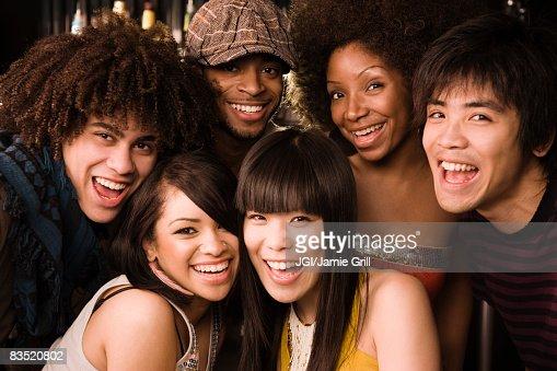 Multi-ethnic friends posing in nightclub : Stock Photo