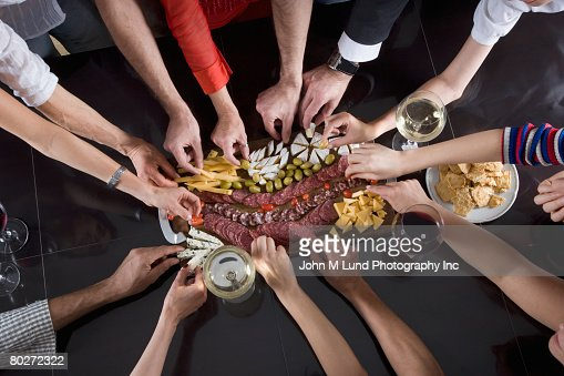 Multi-ethnic friends reaching for food at party : Foto stock