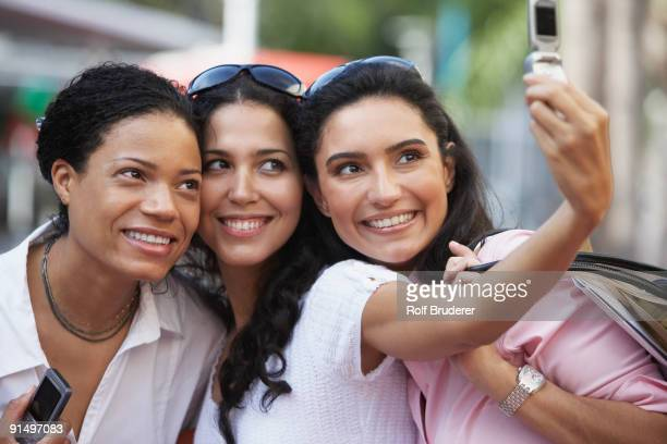 Multi-ethnic friends taking own photograph