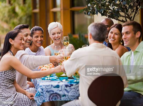 Multi-ethnic friends toasting at party