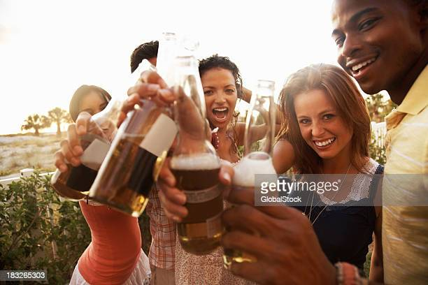 Multi-ethnic friends toasting beer bottle on a vacation
