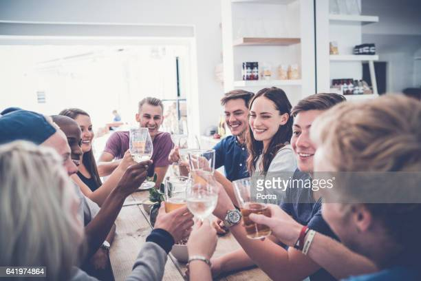 Multi-ethnic friends toasting drinks in restaurant