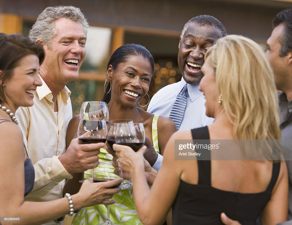 Multi-ethnic friends toasting with wine : Stock Photo