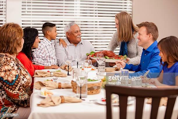 Multi-ethnic, generation family enjoys thanksgiving dinner.