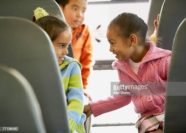 Multi-ethnic girls talking on school bus