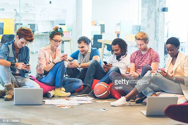 Multi-ethnic Gorup of Creative Young People typing on their phones.