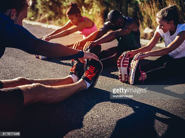 Multi-ethnic group of athletes doing hamstring stretch exercise outside