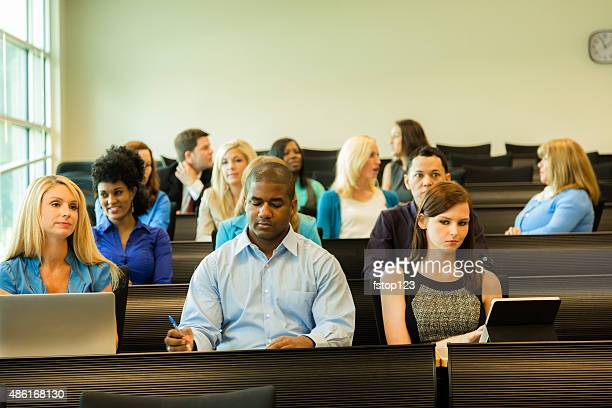 Multi-ethnic group of bored college students in classroom.
