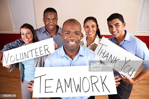 Multi-ethnic group of business professionals with signs. Teamwork, thank you.