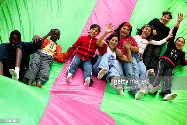 A multiethnic group of cheerful children is playing and laughing on a bouncy slide on July 3 2004 in Sarcelles a Paris suburb France