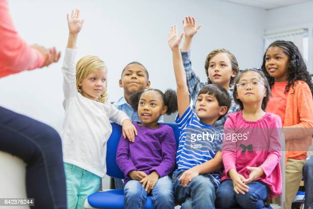 Multi-ethnic group of children in class raising hands