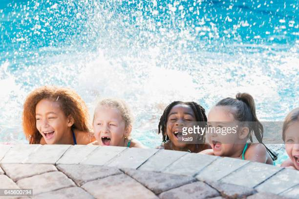 Multi-ethnic group of children in swimming pool laughing