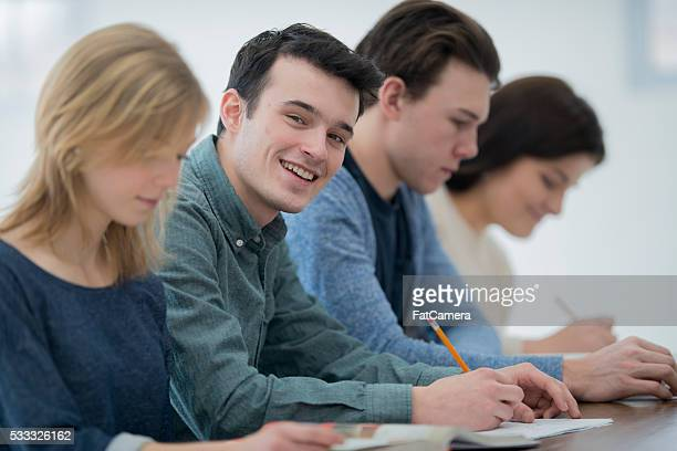 A multi-ethnic group of college age students are sittting