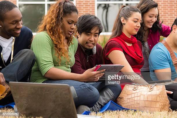 Groupe de Multi ethnique étudiants des amis. Tablette numérique et ordinateur portable.