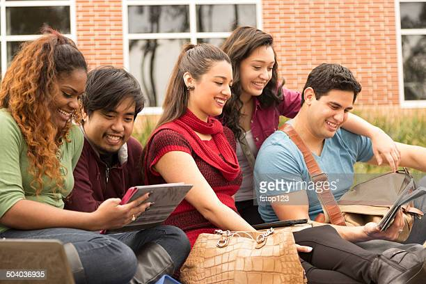 Multi-ethnic group of college student friends. Digital tablet.