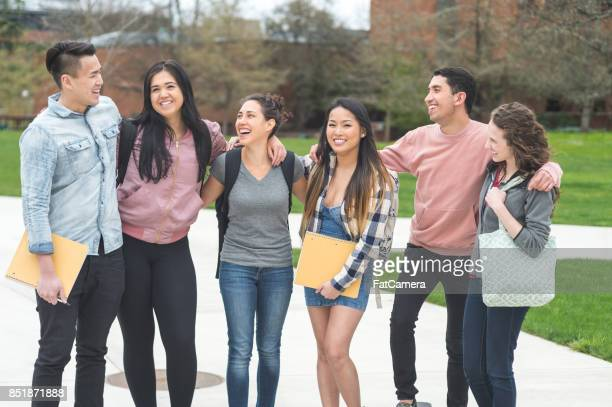 Multiethnic group of college students stand on the sidewalk to pose for a picture together