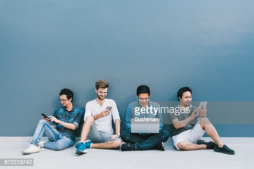 Multiethnic group of four men using smartphone, laptop computer, digital tablet together with copy space on blue wall. Lifestyle with infomation technology gadget, education, or social network concept : Stock Photo