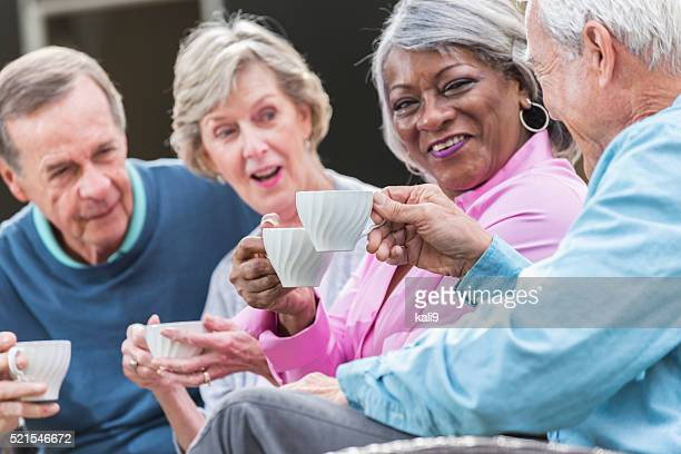 Multi-ethnic group of four seniors sitting outdoors