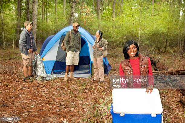 Multi-ethnic group of friends camping in tent outdoors. Autumn.