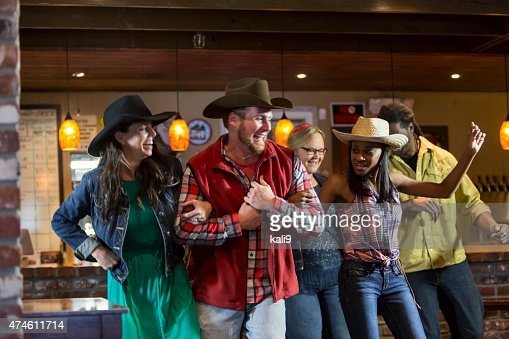 Multi-ethnic group of friends dancing in a bar