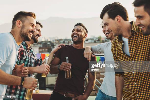 Multi-ethnic group of men laughing and drinking beer