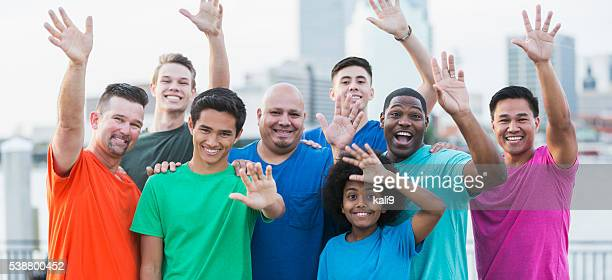 Multi-ethnic group of men waving