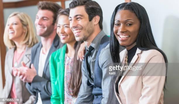 Multi-ethnic group of men, women watching presentation