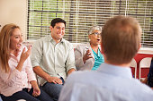 Multi-ethnic group of people in counseling session with therapist.