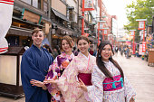 Multi-Ethnic group of people in kimono standing in traditional Japanese town