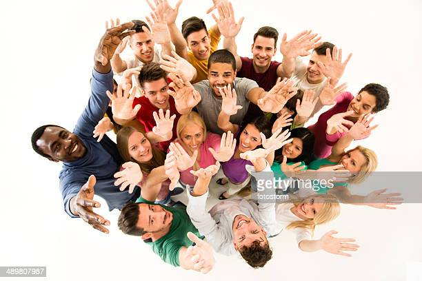 Multiethnic group of people with hands raised