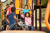 Multi-ethnic group of school children playing on school playground.  African descent, elementary age boy is in a wheelchair.  Other children, play and talk to boy in front of outdoor playground equipm