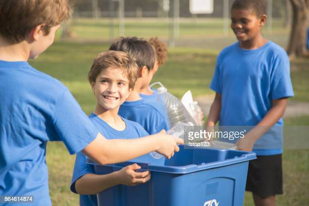 Multi-ethnic group of school children recycling at park.