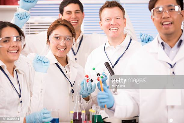 Multi-ethnic group of scientists in research laboratory. Excited about discovery.