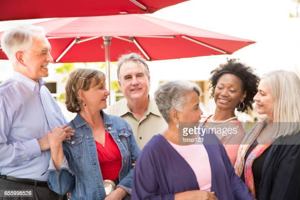 Multi-ethnic group of senior adult friends enjoy visiting at outdoor cafe.