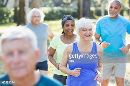 Multi-ethnic group of seniors running in park : Stock-Foto
