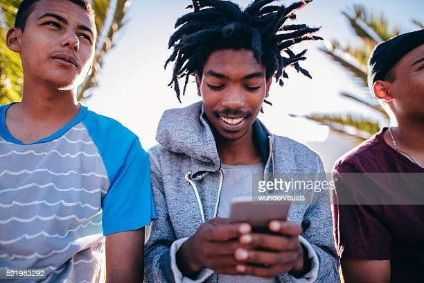 Multi-ethnischen eine Gruppe von Skater im Freien sitzen und schaut an SM einem