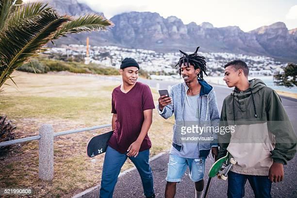 Multi-ethnischen eine Gruppe von Skater zu Fuß am Strand entlang Straße