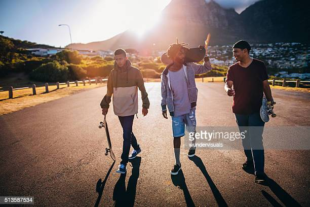 Multi-Ethnic Group of Skaters Walking Down Street at Seaside