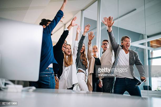 Multi-ethnic group of start up colleagues celebrating successful presentation pitch.