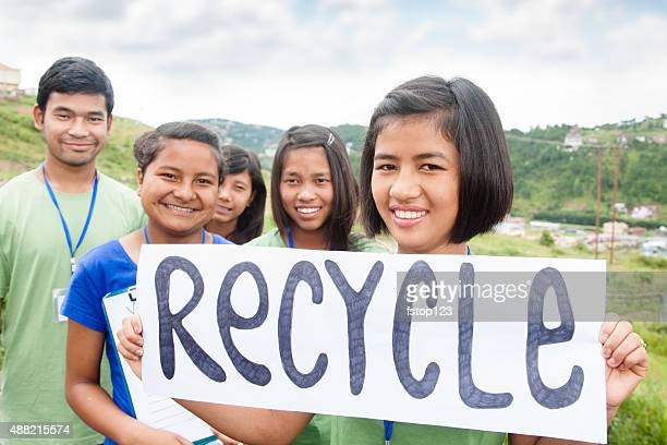 Multi-ethnic group of teenagers hold 'recycle' sign outdoors.