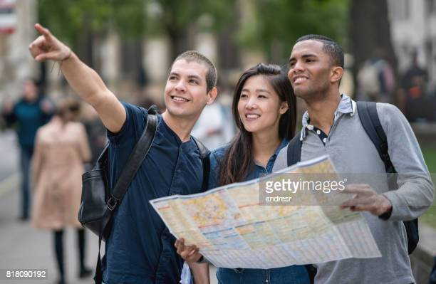 Multi-ethnic group of tourists in London holding a map and pointing away