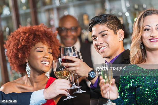 Multi-ethnic group of young adults at a bar drinking