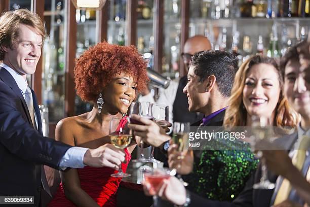 Multi ethnique groupe de jeunes adultes de prendre un verre au bar