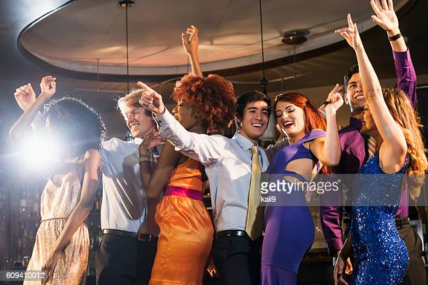 Multi-ethnic group of young adults dancing at club